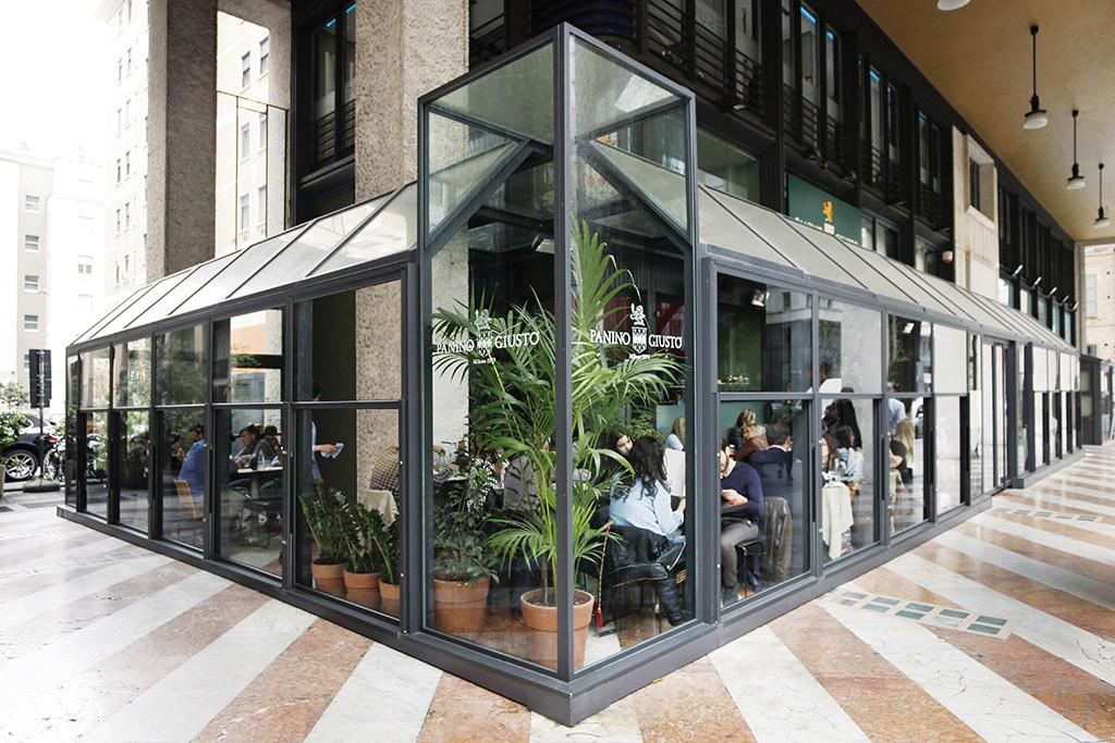 dehors in vetro di un ristorante realizzato con paraventi da esterno in alluminio ad altezza regolabile saliscendi colore ferro micaceo modello up&down di Star Progetti