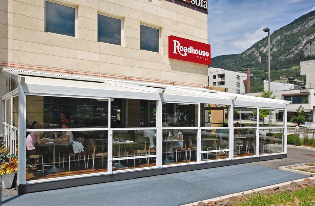 dehors in vetro di un ristorante realizzato con paraventi in vetro da esterno saliscendi colore bianco modello up&down e pedana di Star Progetti