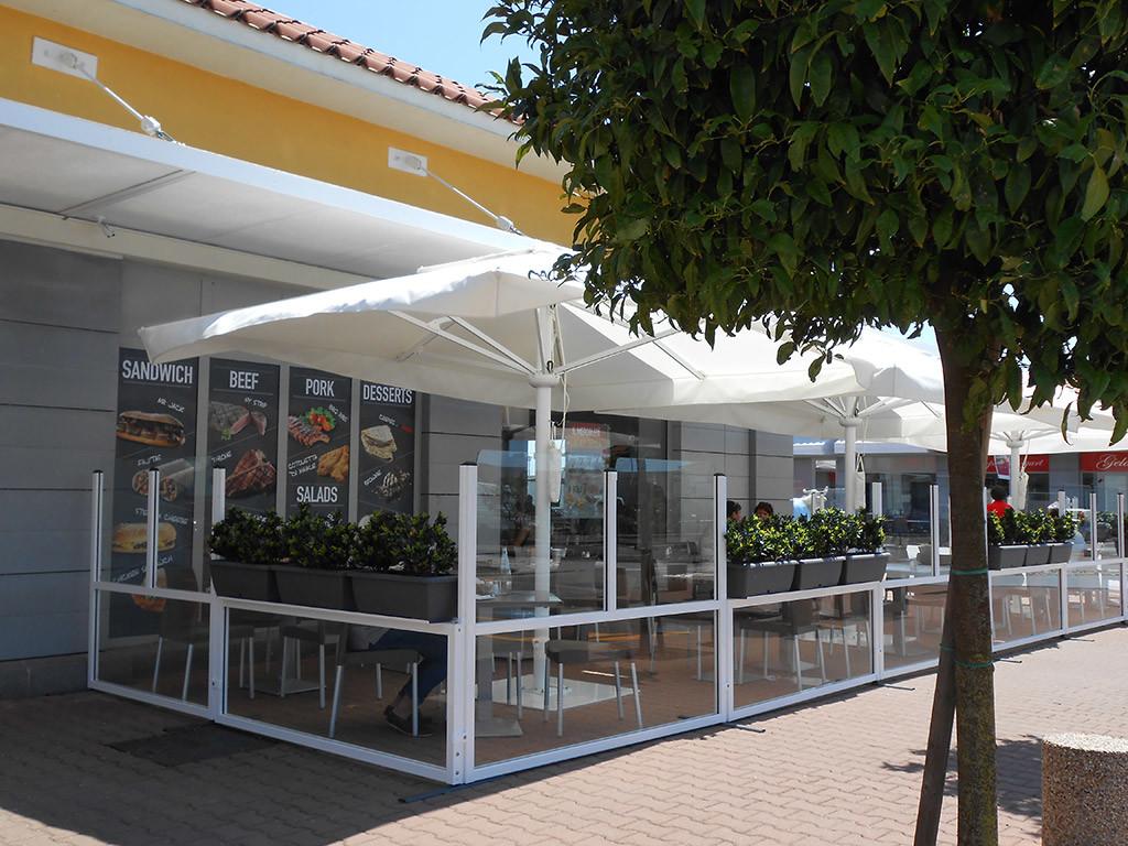 dehors di un ristorante realizzato con paraventi in vetro per esterno con fioriera colore bianco modello elegance di Star Progetti