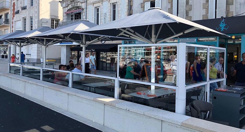 dehors di un bar vista mare realizzato con paraventi da esterno ad altezza regolabile Taormina di Star Progetti e riscaldato dalle lampade a raggi infrarossi di heliosa di star progetti