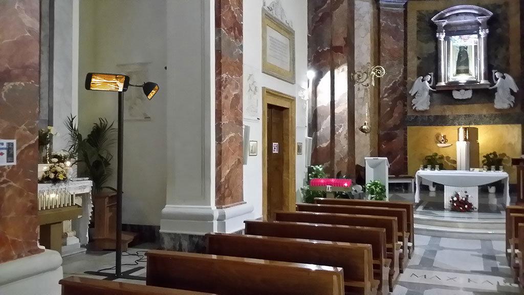 panche dei fedeli all'interno di una chiesa riscaldate con fungo elettrico nero helios tower di star progetti