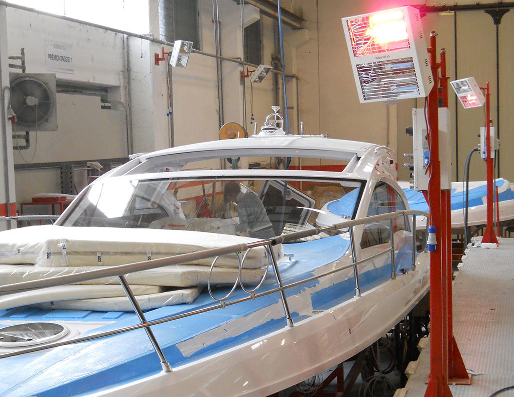 lampade riscaldanti a raggi infrarossi di star progetti vengono utilizzate per favorire l'asciugatura della vetroresina in un cantiere di costruzioni navali
