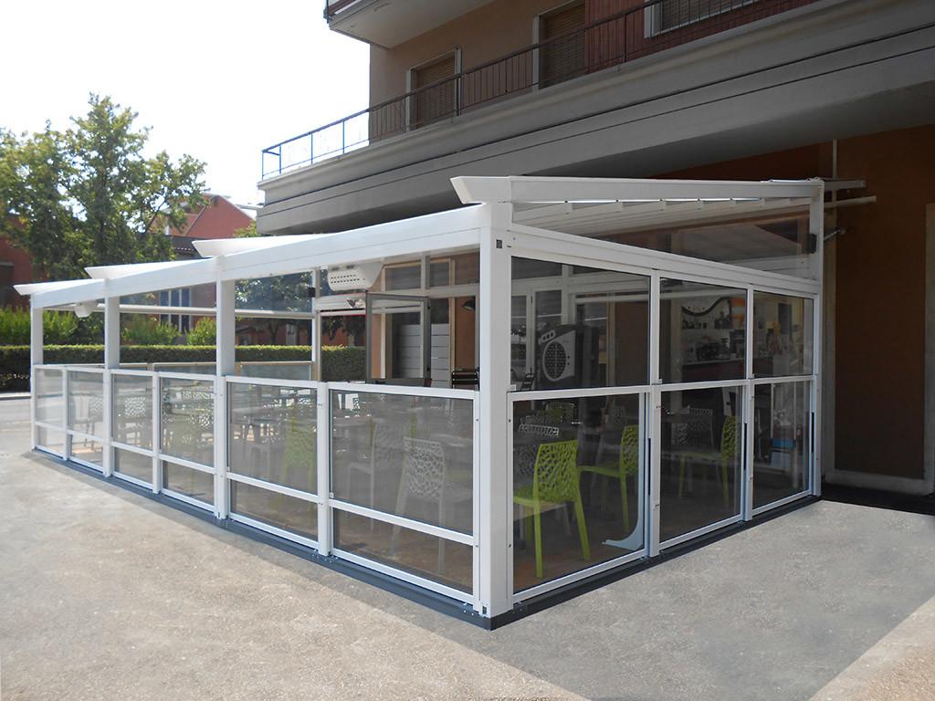 dehors esterno di un ristorante realizzato con i paraventi da esterno saliscendi tuttovetro colore bianco e pedana di Star Progetti