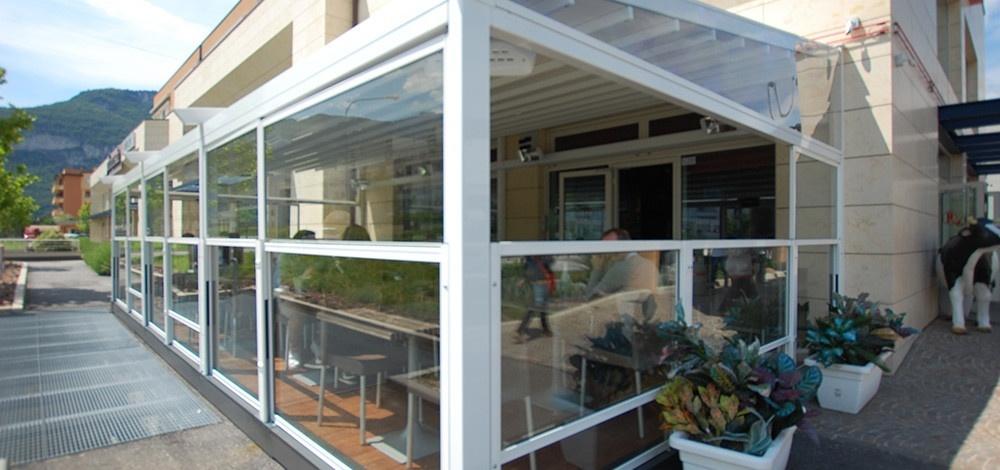dehors esterno di un bar realizzato con i paraventi saliscendi in alluminio e vetro colore bianco di Star Progetti