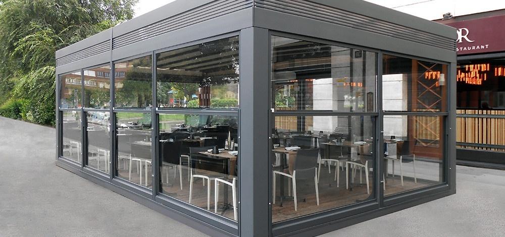 dehors esterno di un ristorante realizzato con i paraventi saliscendi in alluminio colore ferro micaceo e vetro di Star Progetti
